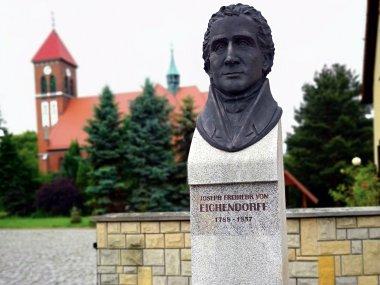Łubowice - popiersie Eichendorffa, w tle kościół parafialny, fot. Ewa Gatnar